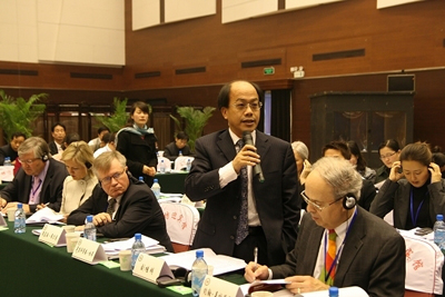 A participant poses a question to expert panelists during a November 2009 symposium on mediation in Langfang, China.