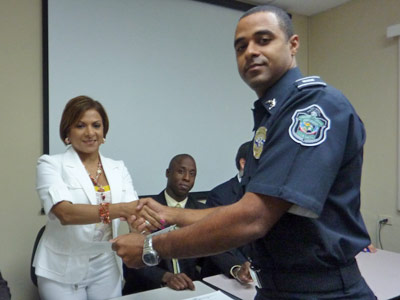 ABA ROLI Legal Reform Coordinator Waleska de Segovvia presents a certificate to Lieutenant Ricardo Davis who completed a recent training and was interviewed for this story..